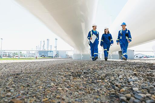 Pipeline safety - Three people walking under pipeline